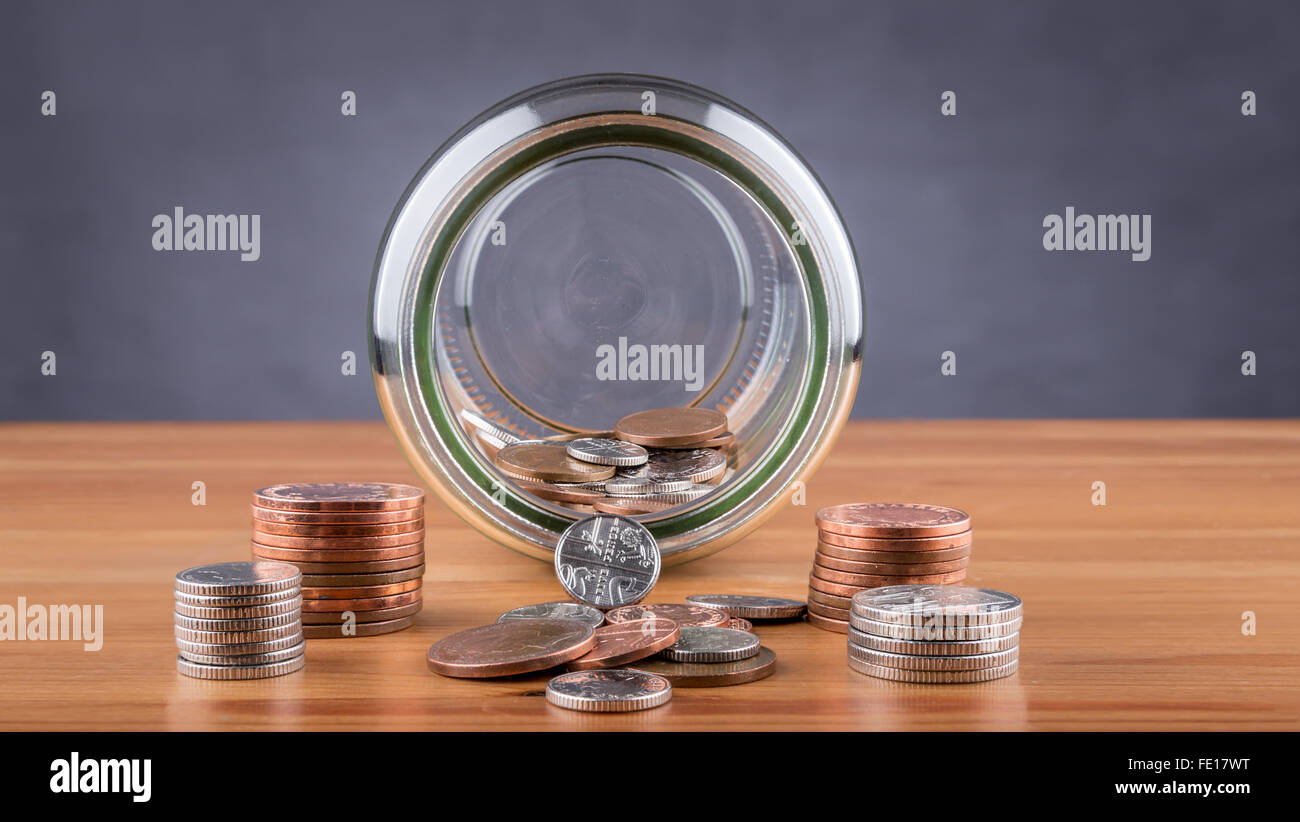 A savings jar with a small number of coins. Stock Photo