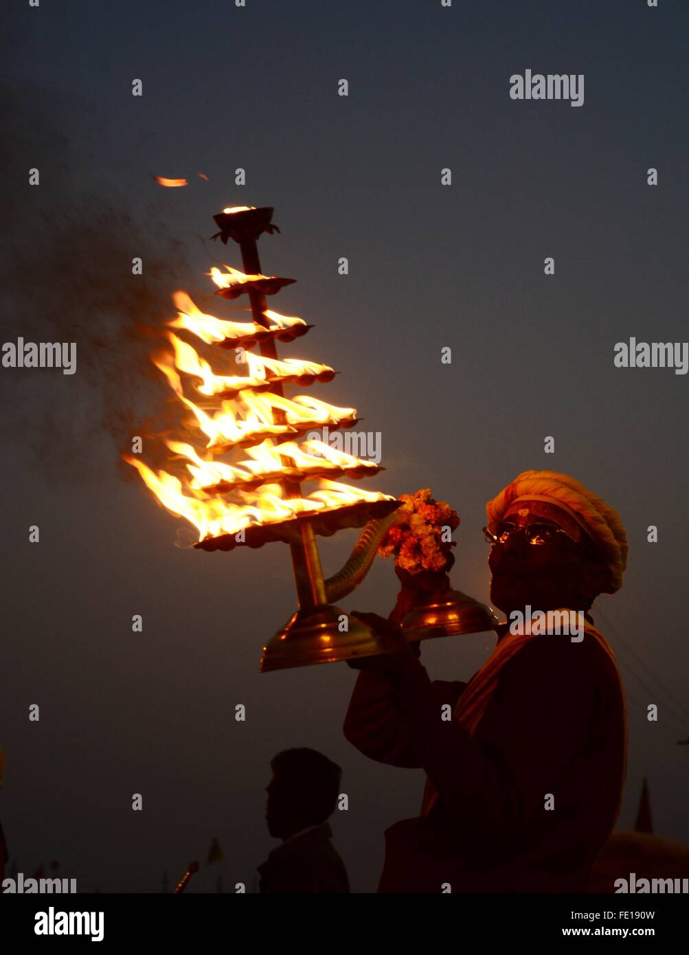 Allahabad, India. 03rd Feb, 2016. A priest rotates the traditional oil lamp as he offer evening prayer at Sangam, - Stock Image
