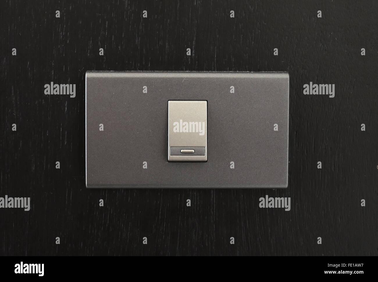 Black toggle switch on black surface - Stock Image