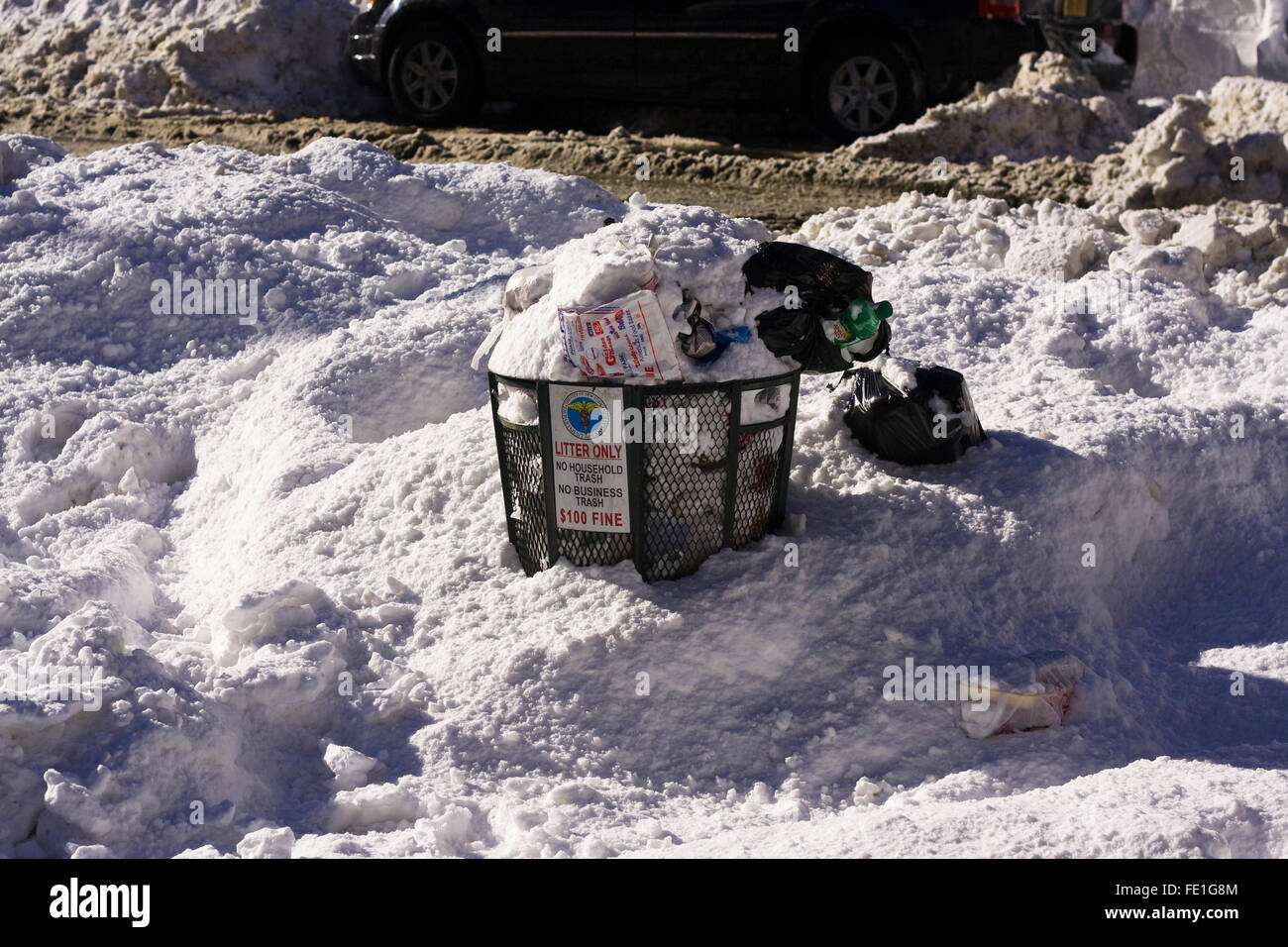Overflowing Trash Can partially covered in 2 feet of snow on a street corner in New York City - Stock Image