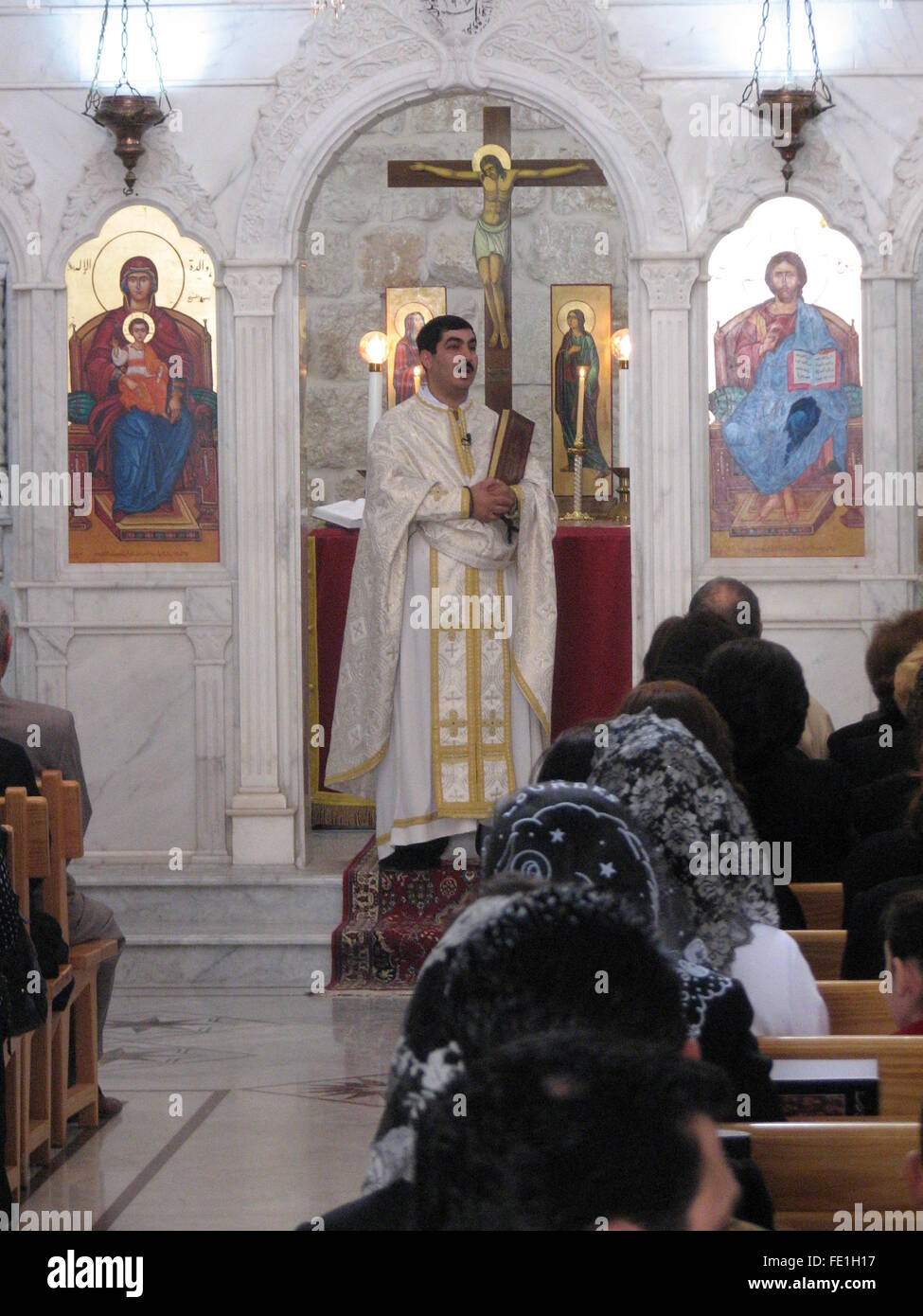 Christian Priest giving the Sunday Mass Prayer in Arabic at
