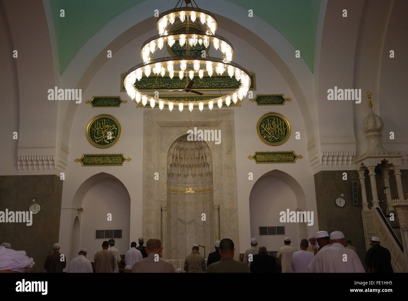 Worshipers in front of the Mehrab in Masjid Quba, the very first Mosque that was built, Medina, Saudi Arabia - Stock Image