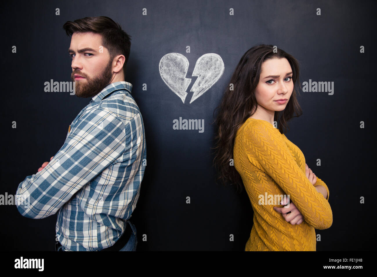 Unhappy young couple standing with arms crossed over background of chalkboard with drawn broken heart - Stock Image