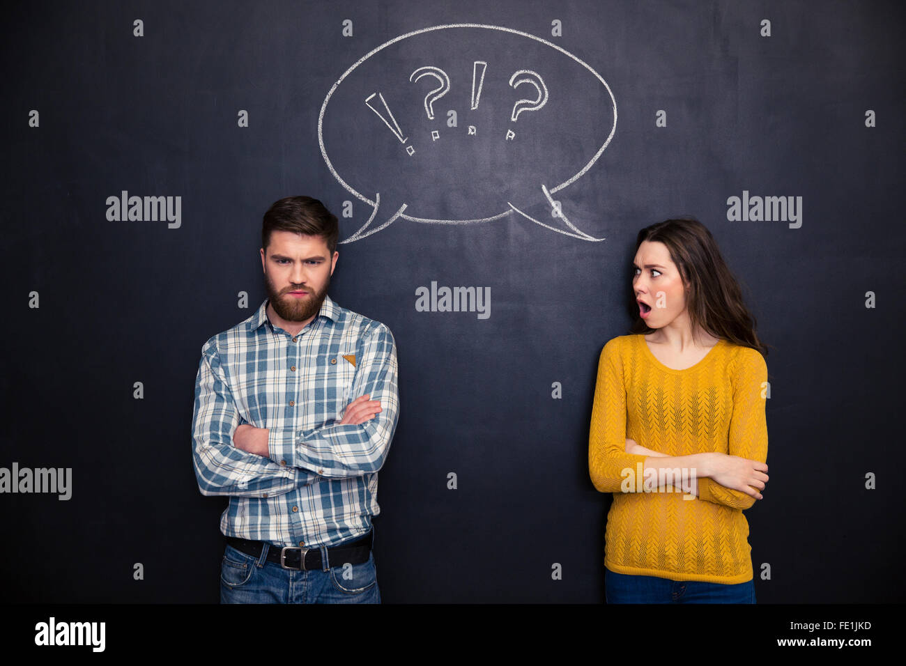 Frowning offended young couple standing with arms crossed after argument over chalkboard background - Stock Image