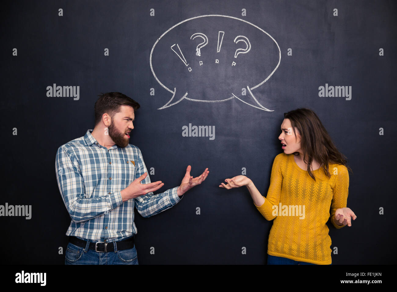 Unhappy young couple standing and quarreling over blackboard background - Stock Image