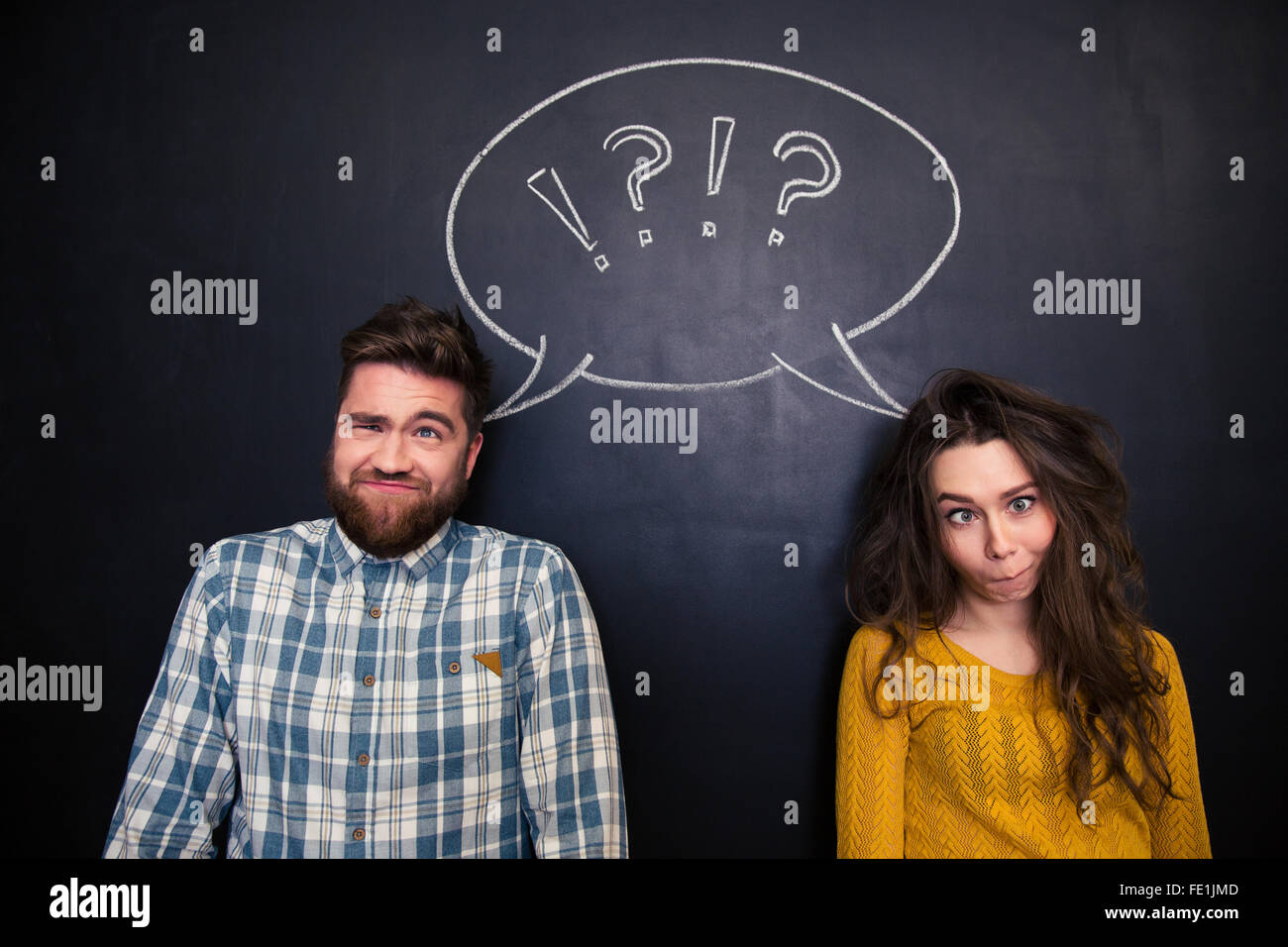 Ugly young couple joking and grimacing over chalkboard background - Stock Image