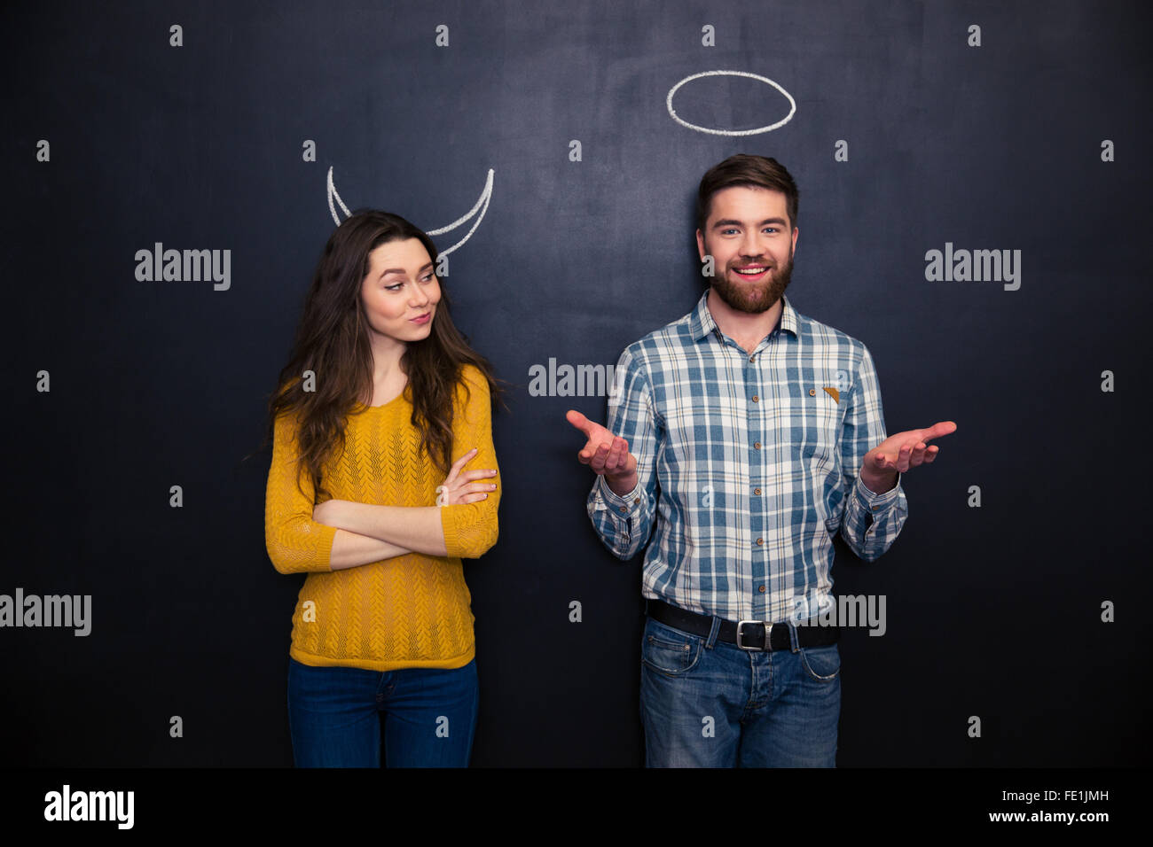 Happy young couple playing roles of devil and angel standing over blackboard background Stock Photo