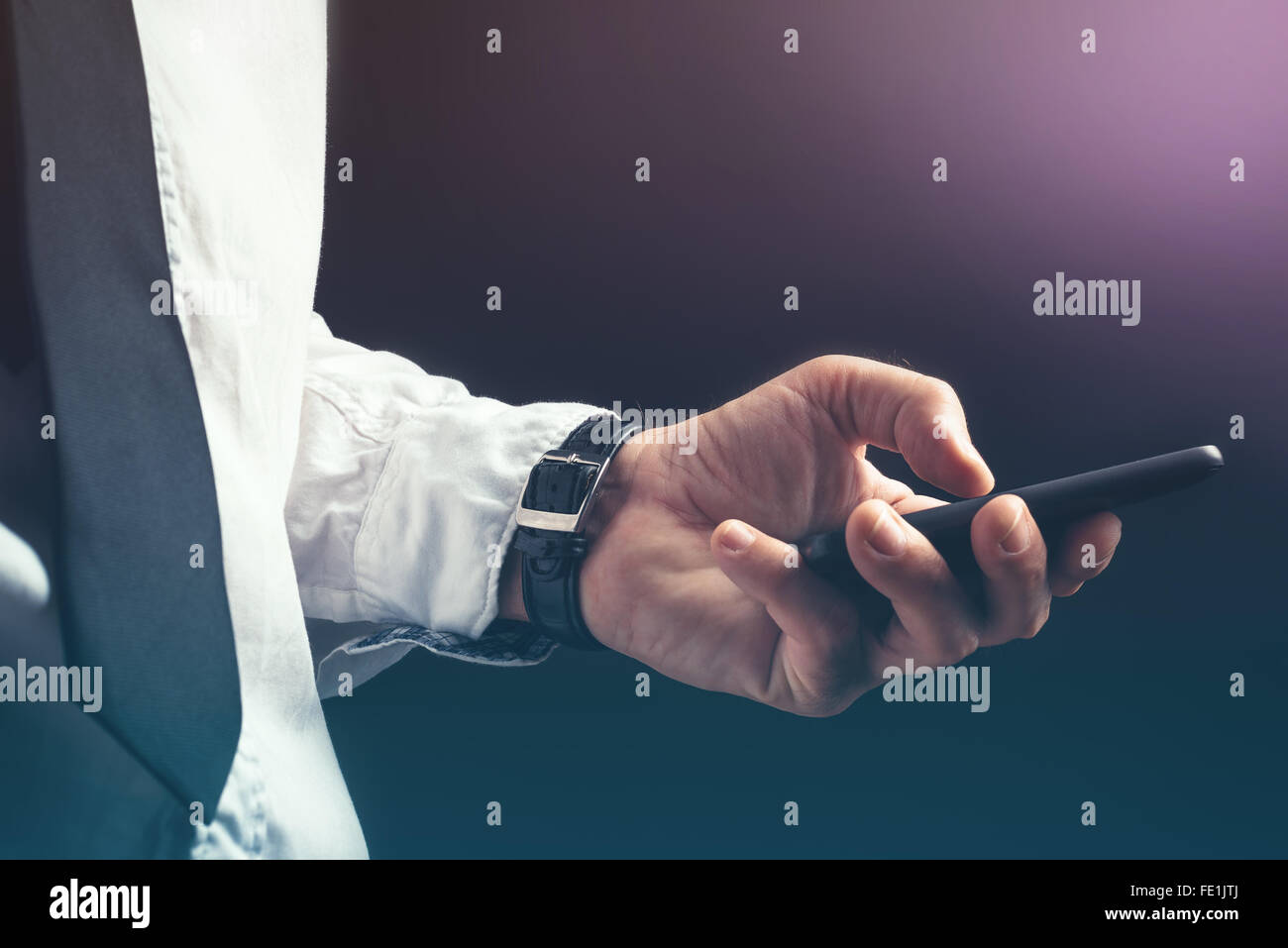 Young unrecognizable businessman professional texting on smartphone using message app in dark office interior. - Stock Image