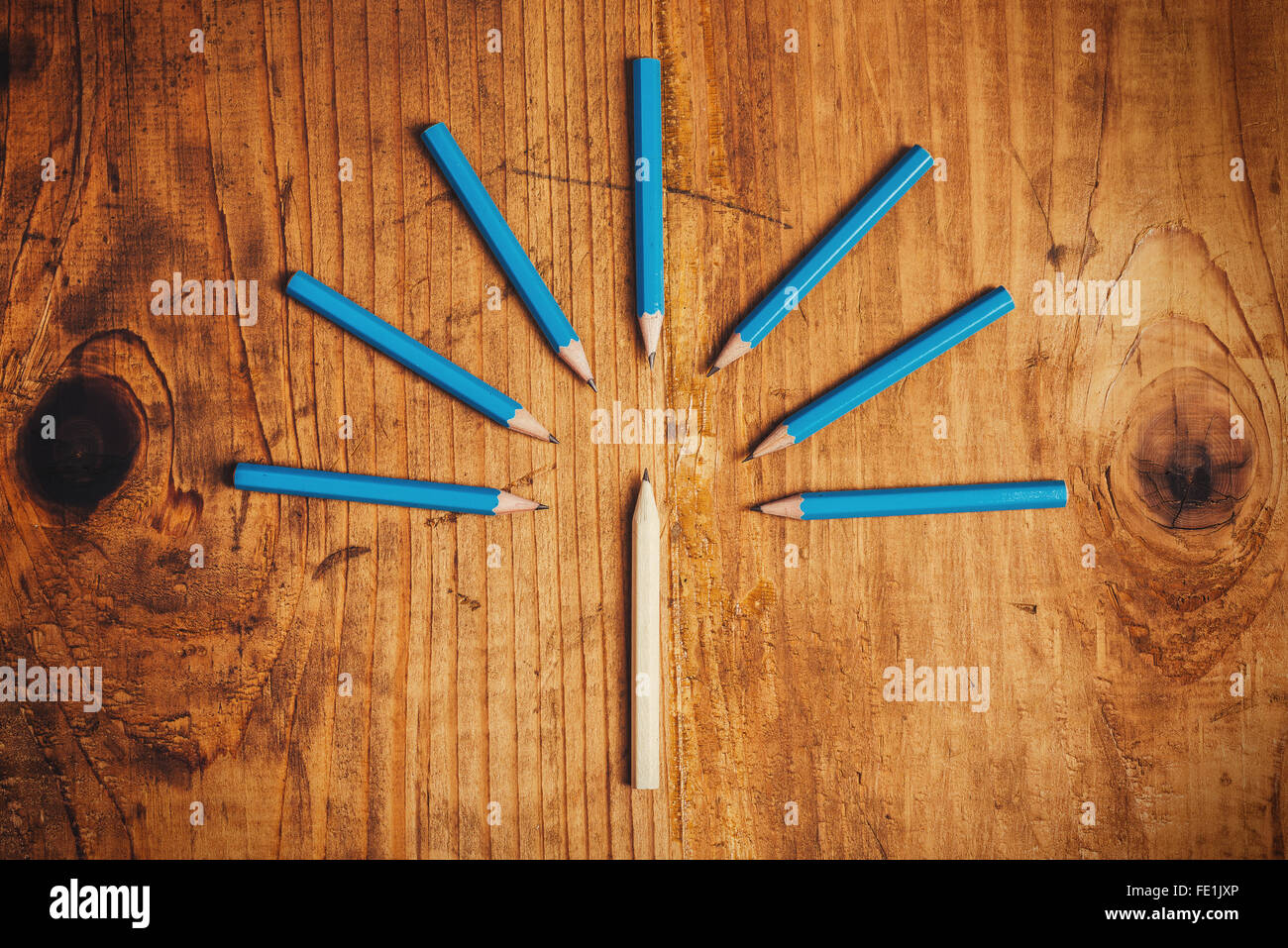 Being different concept, surrounded by adversity, judging the odd one, wood pencils on desk - Stock Image