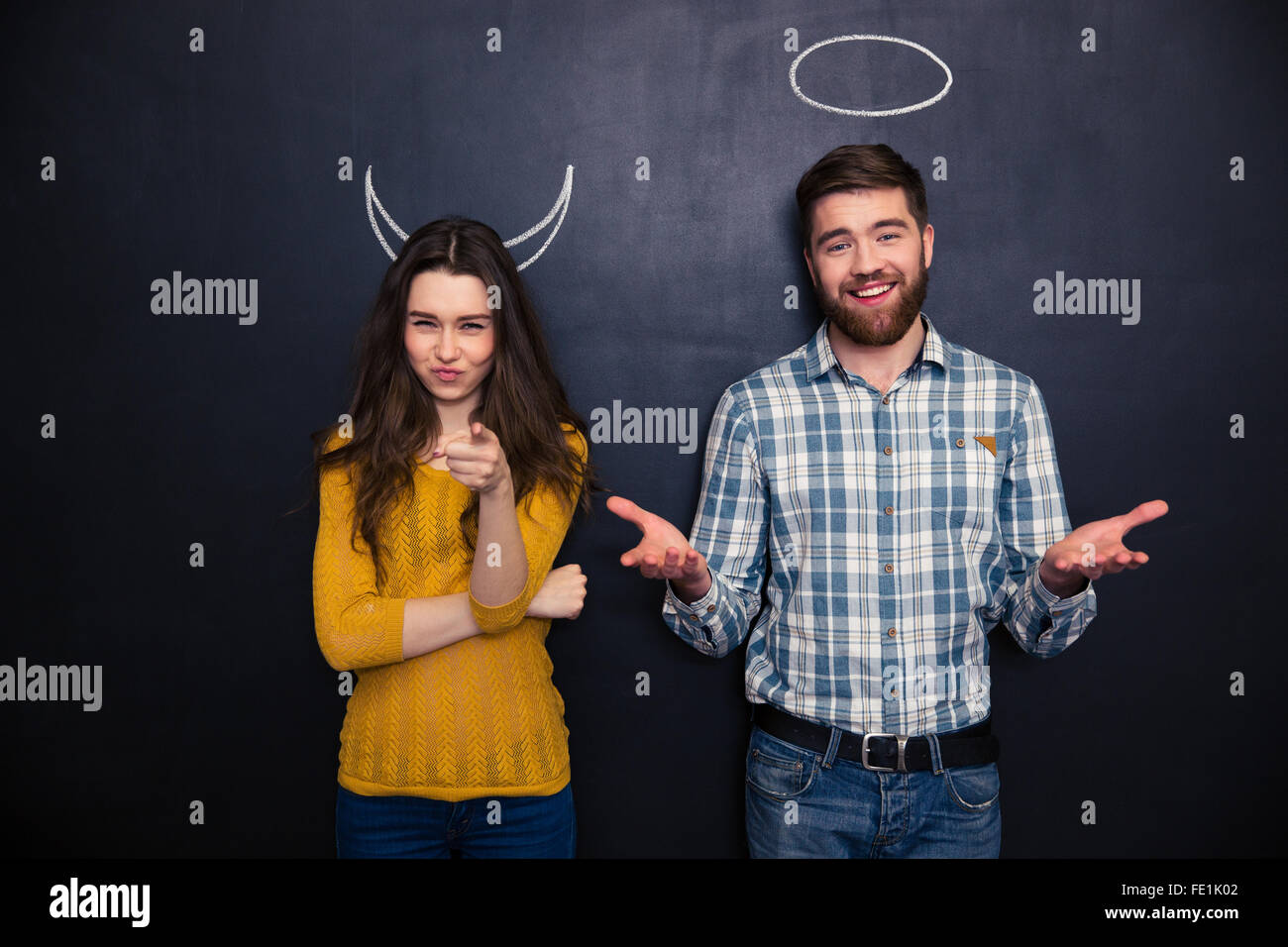 Beautiful young couple standing over blackboard background with drawn hornes and halo and pointing on you Stock Photo