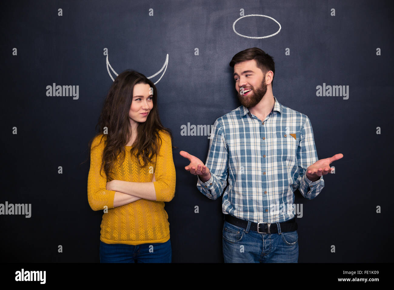 Smiling young man and woman imitating devil and angel standing over chalkboard background Stock Photo