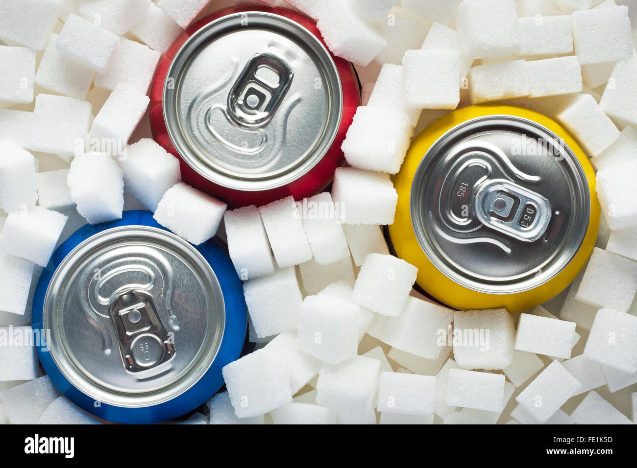 Unhealthy food concept - sugar in carbonated drinks. Sugar cubes as background and canned drinks - Stock Image