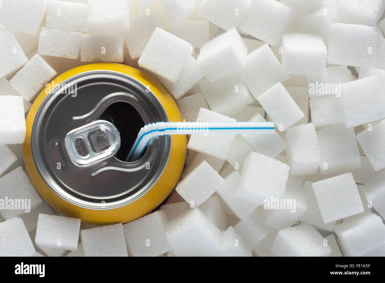 Unhealthy food concept - sugar in carbonated drink. Sugar cubes as background and canned drink - Stock Image