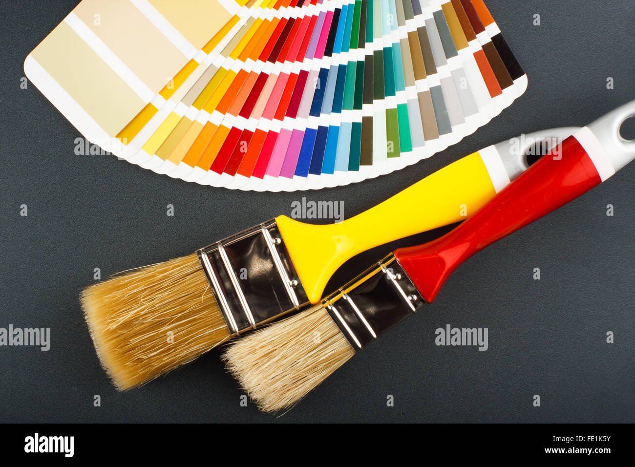 Color card and paint brushes on dark background - Stock Image
