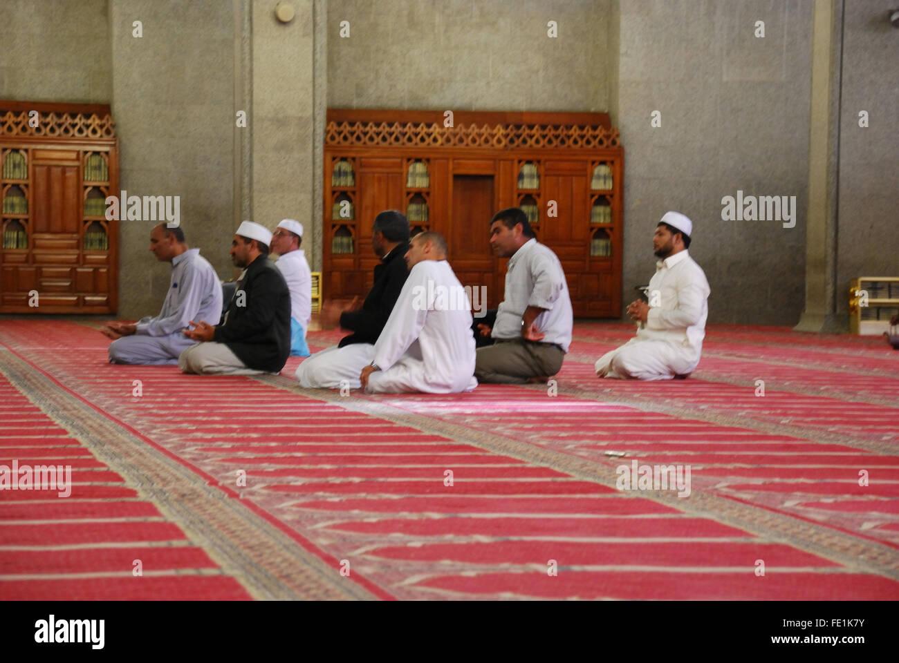 Men inside Masjid Quba, the very first Mosque that was built, Medina, Saudi Arabia - Stock Image