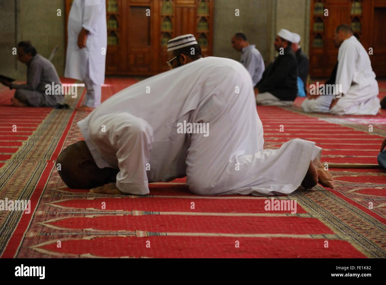 Man prostrating inside Masjid Quba, the very first Mosque that was built, Medina, Saudi Arabia - Stock Image
