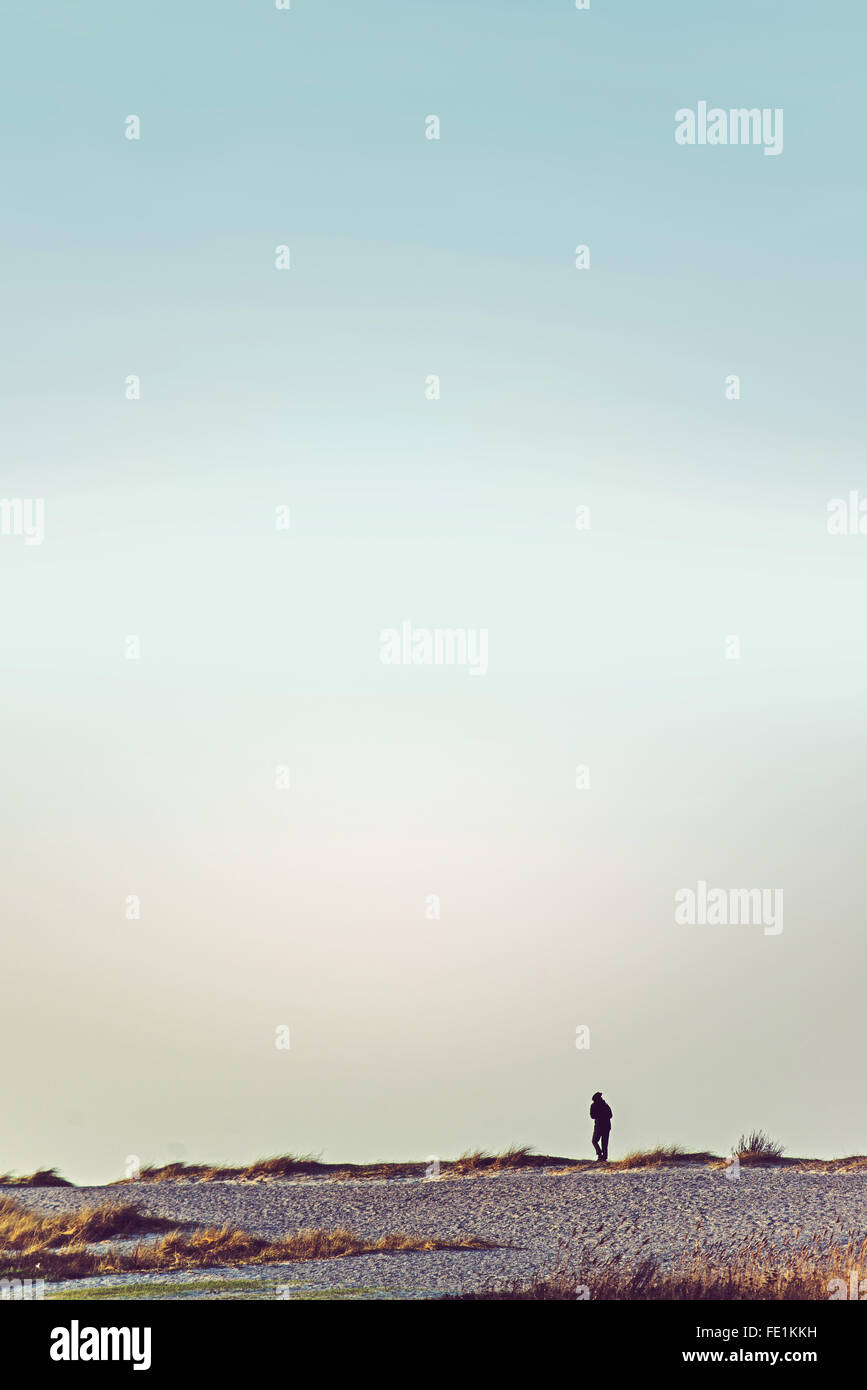 Unrecognizable person walking on wasteland horizon, retro toned image with sky as copy space - Stock Image