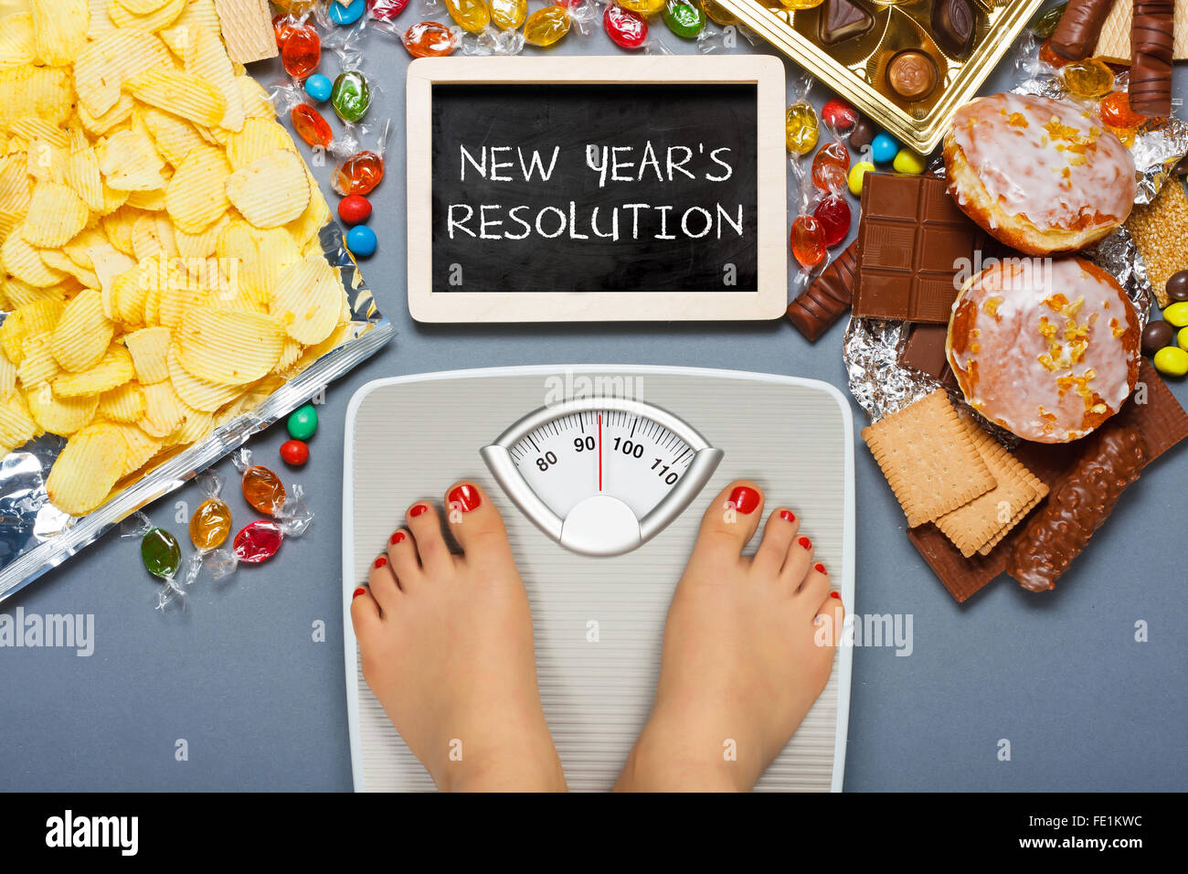 Diet concept. Feet of a young woman on bathroom scale - Stock Image