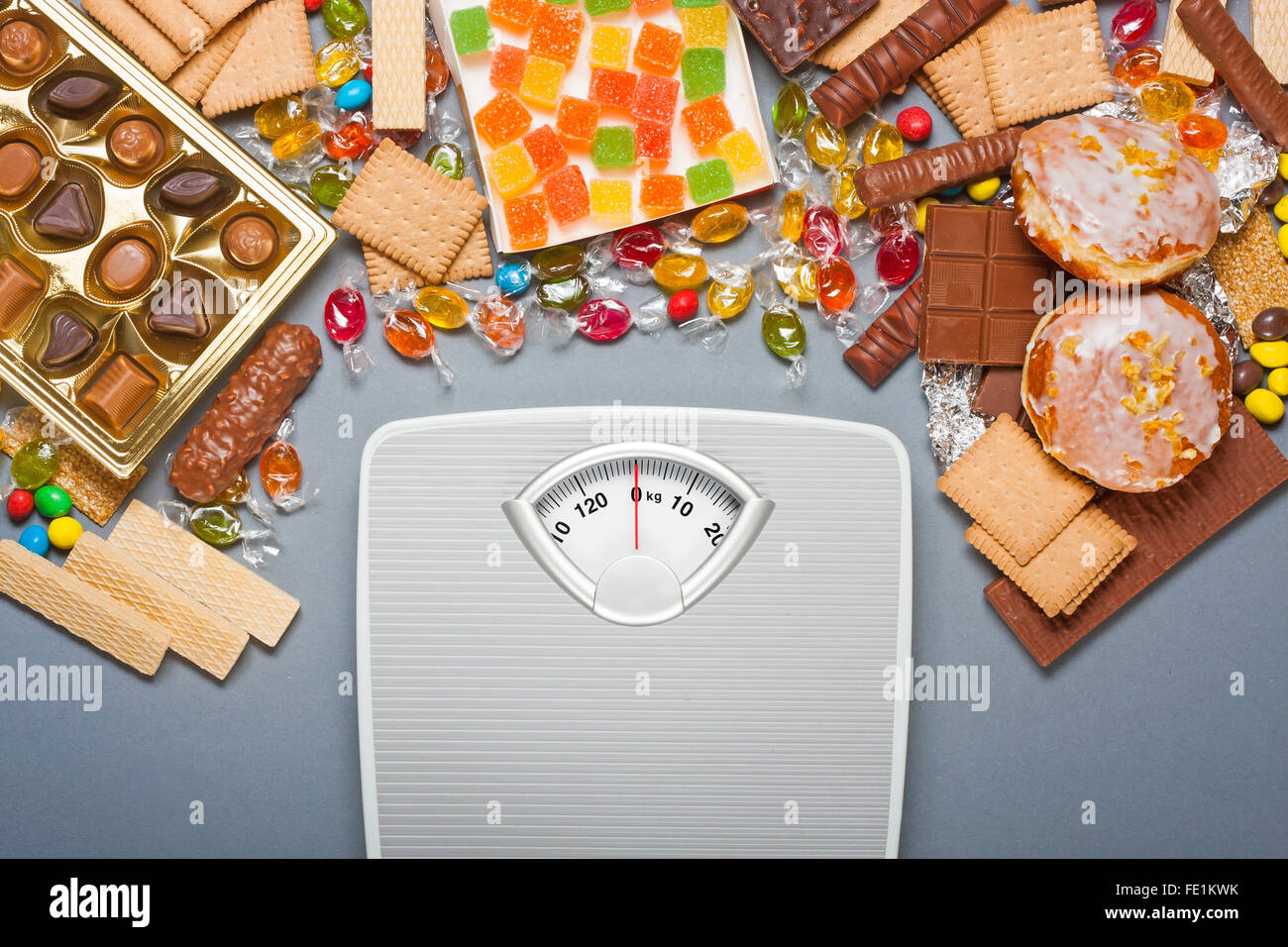 Unhealthy diet concept - overweight. Bathroom scale and chocolate, jelly cubes, candies, chocolate bars, cookies, - Stock Image