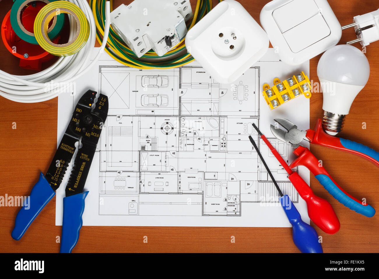 Electrical equipment, tools and house plans on the desk - Stock Image