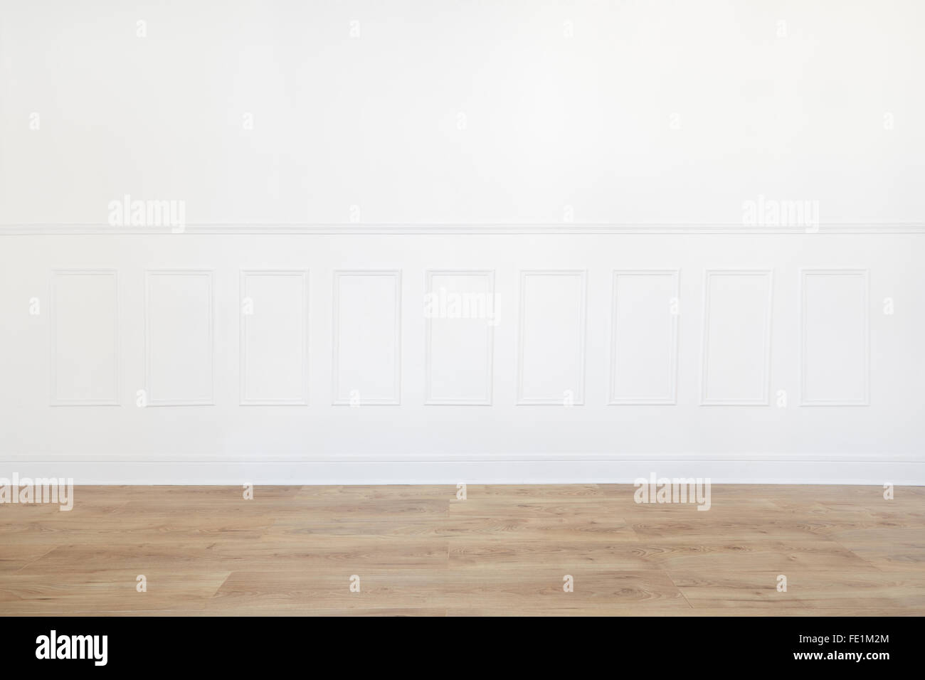 Empty white room with wooden floor and wood trimmed wall - Stock Image