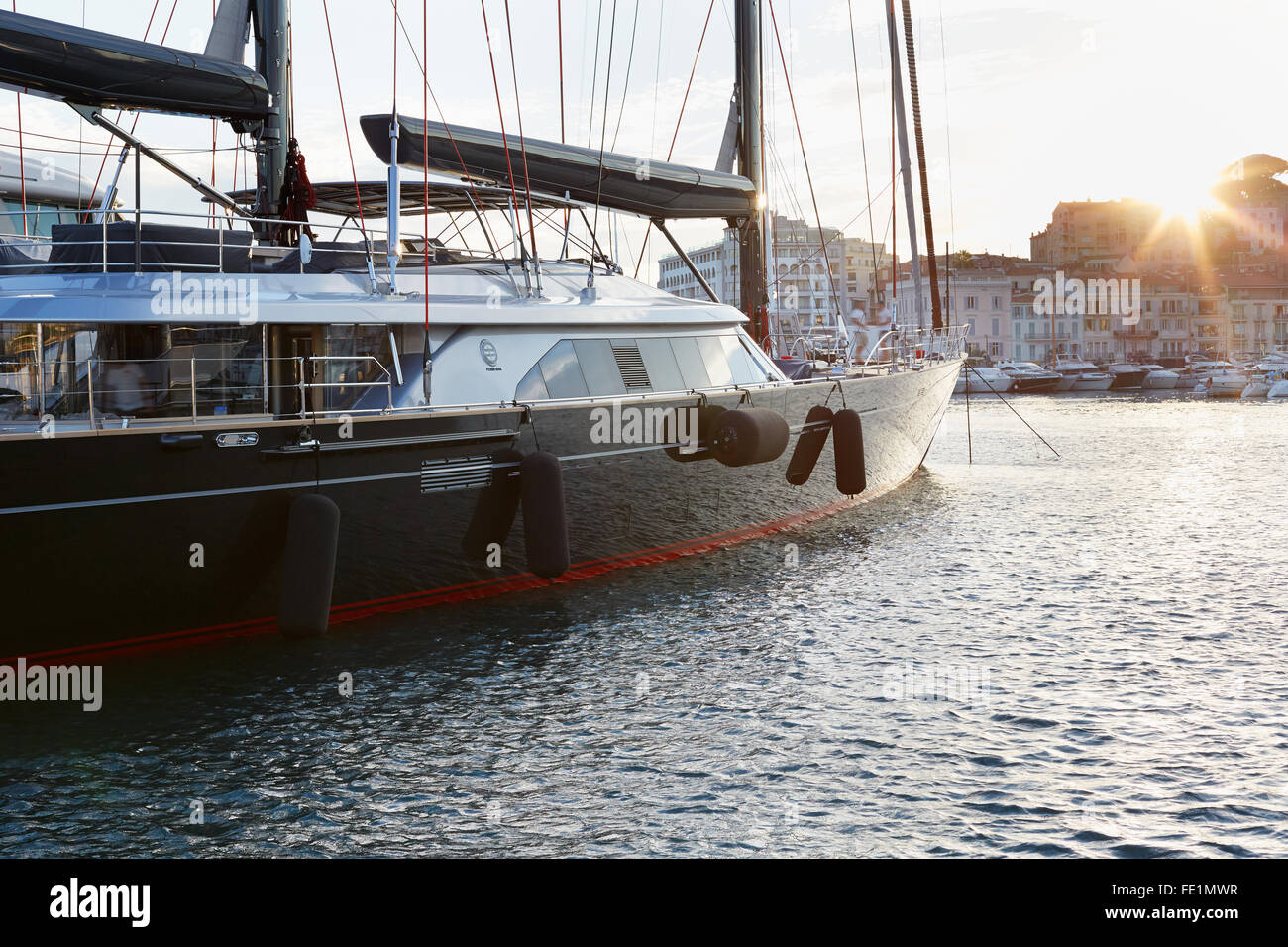 Modern black an red sail boat by Perini navi seen in the harbor in the sunset light, Cannes - Stock Image