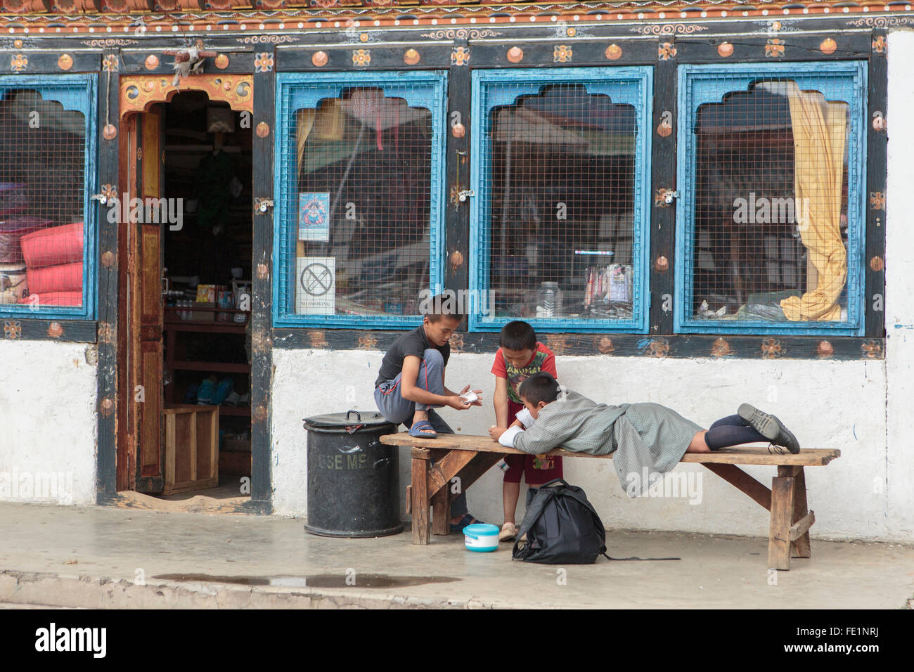 Children play outside a shop in Paro, Bhutan - Stock Image