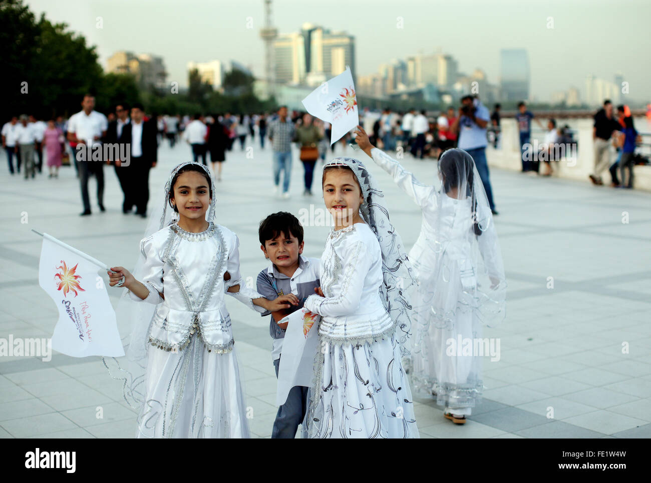 Children in traditional dress on the waterfront city of Baku, Azerbaijan - Stock Image