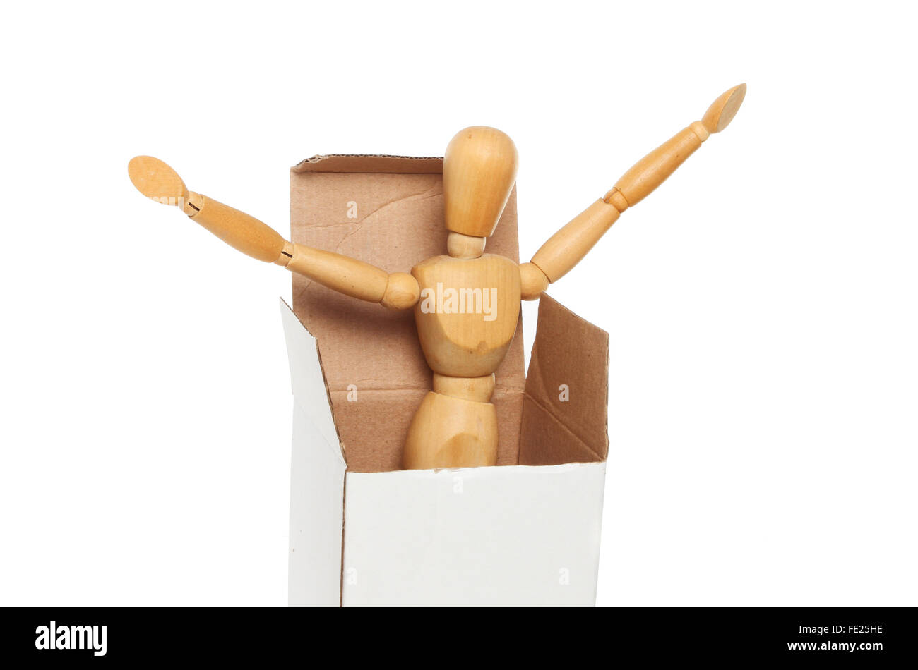 An artist's wooden manikin springs out of a cardboard box isolated against white - Stock Image