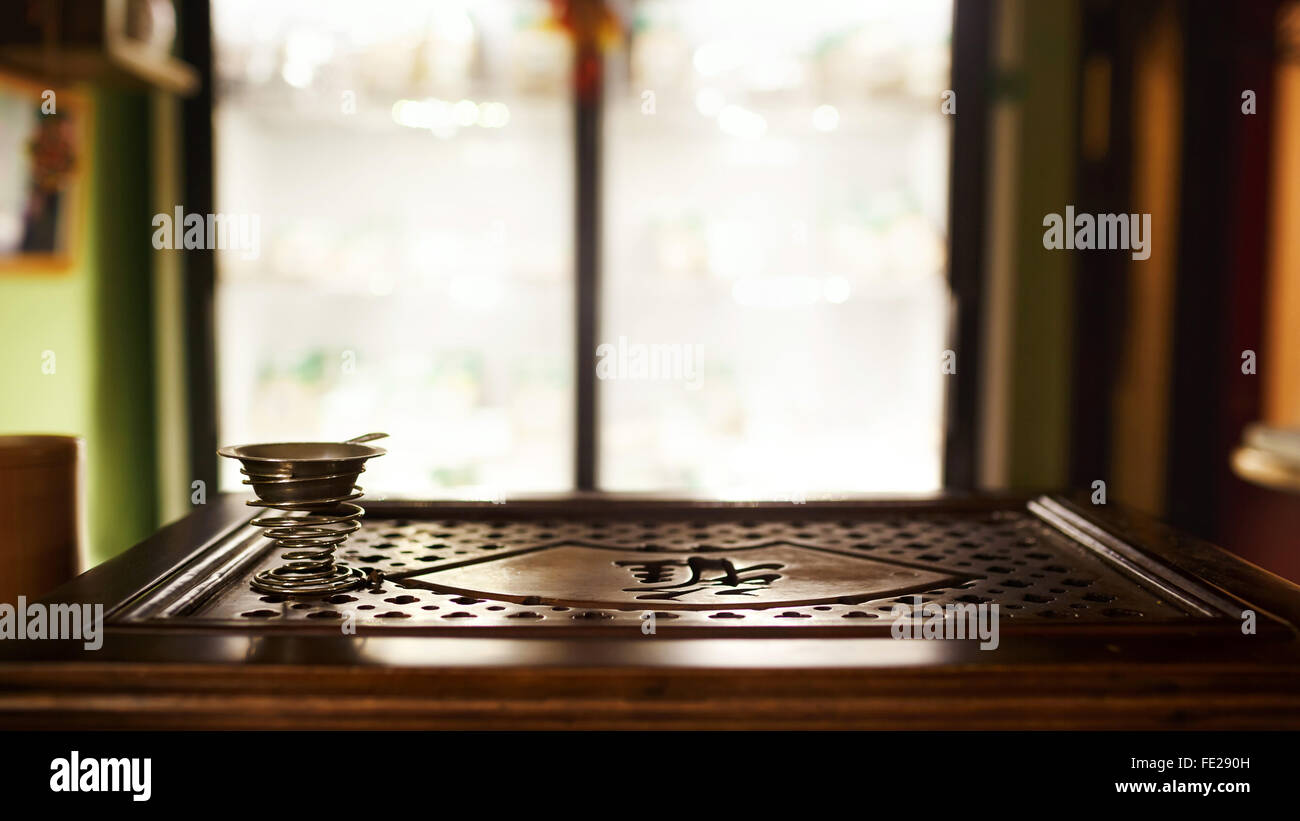 Tea shop with blurred background, tray for traditional ceremony, interior. Shallow depth of field. Metal cup on - Stock Image