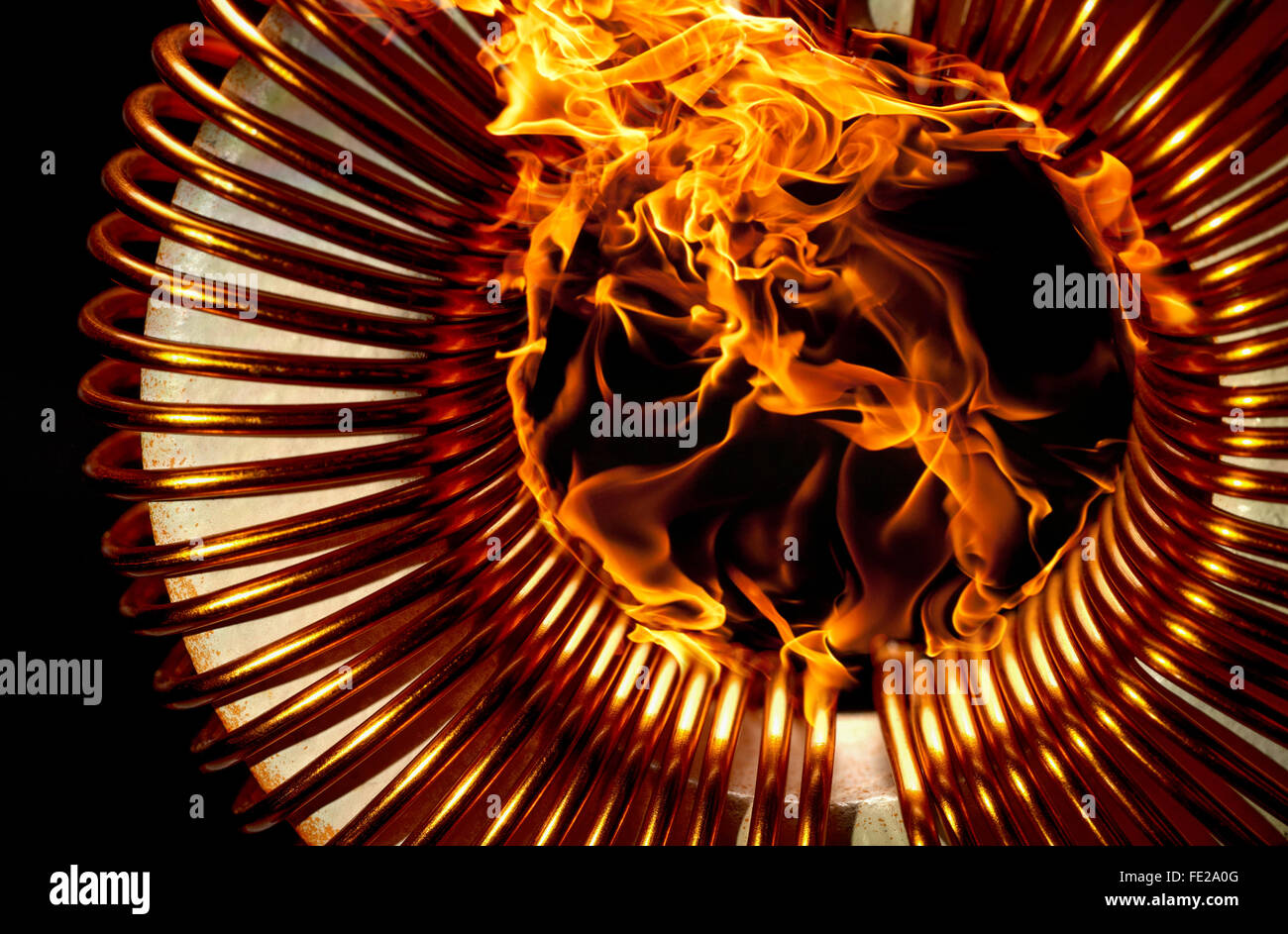 burning inductor coil in black back - Stock Image