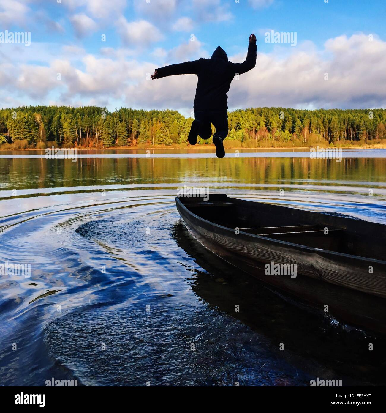 Man Jumping Into Boat - Stock Image