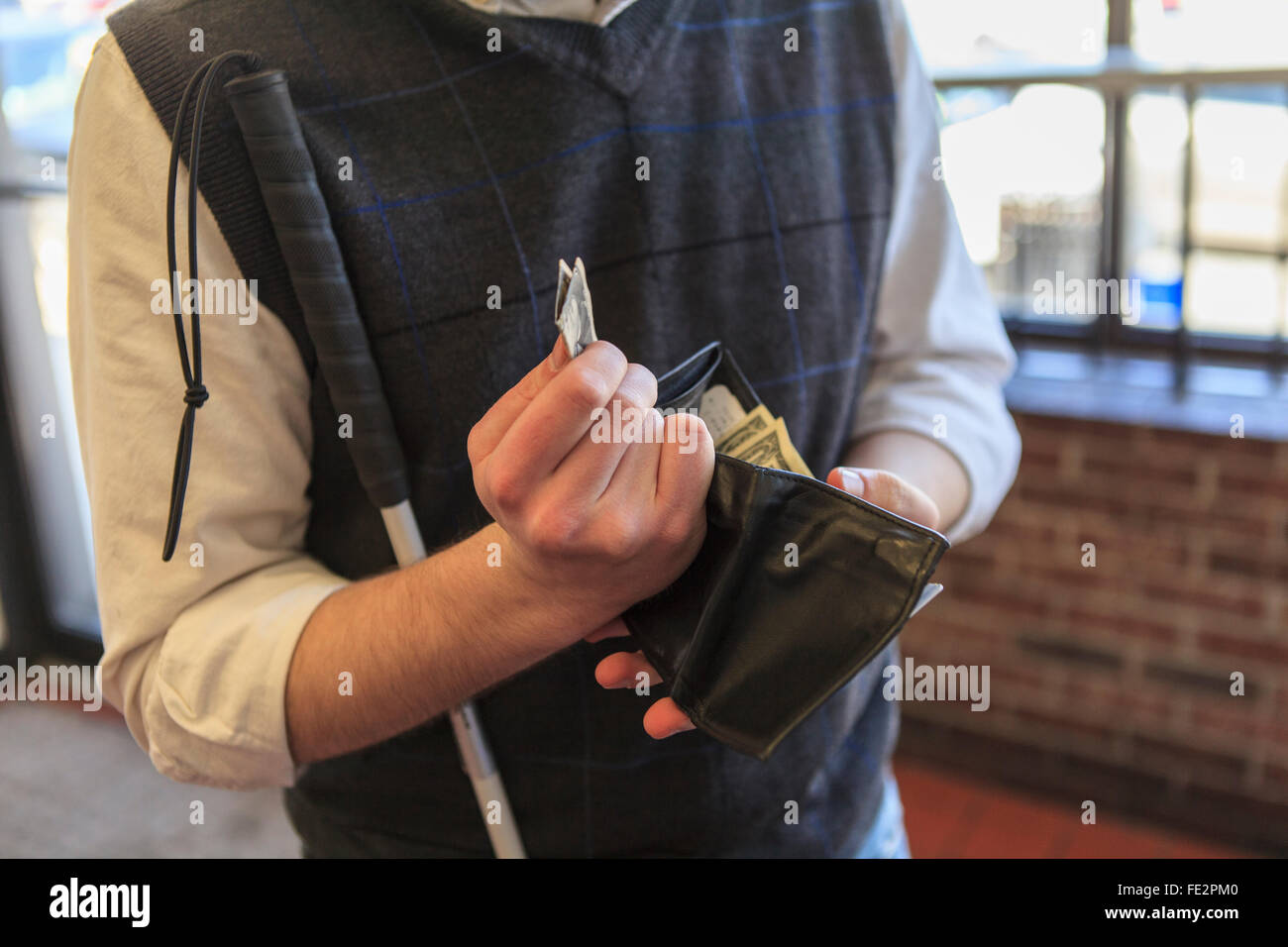 Young blind man with cane counting his money - Stock Image