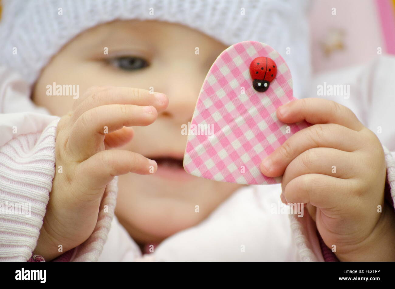 baby wearing a hat holding a heart - Stock Image