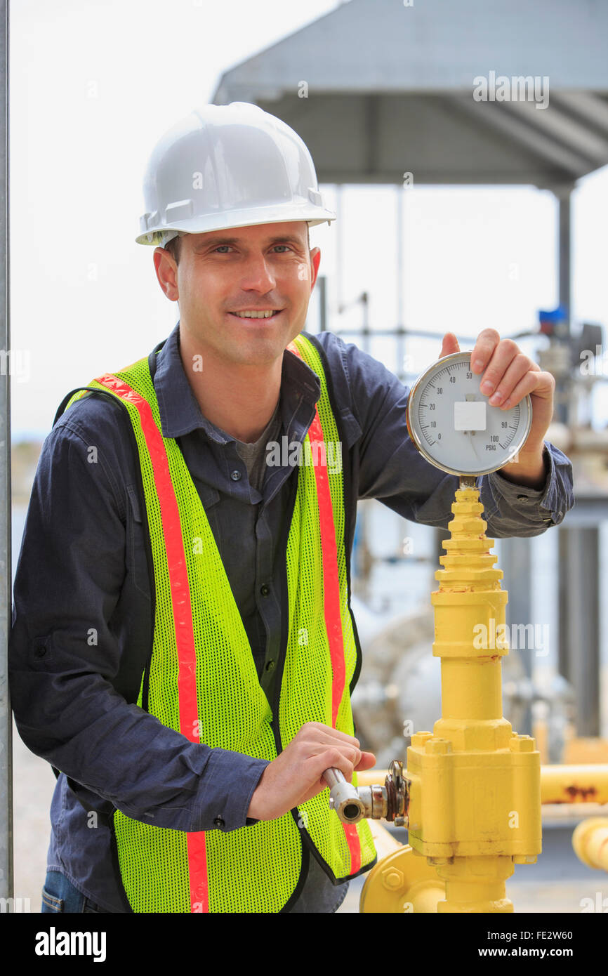 Industrial engineer at analog pressure gauge at a power plant - Stock Image