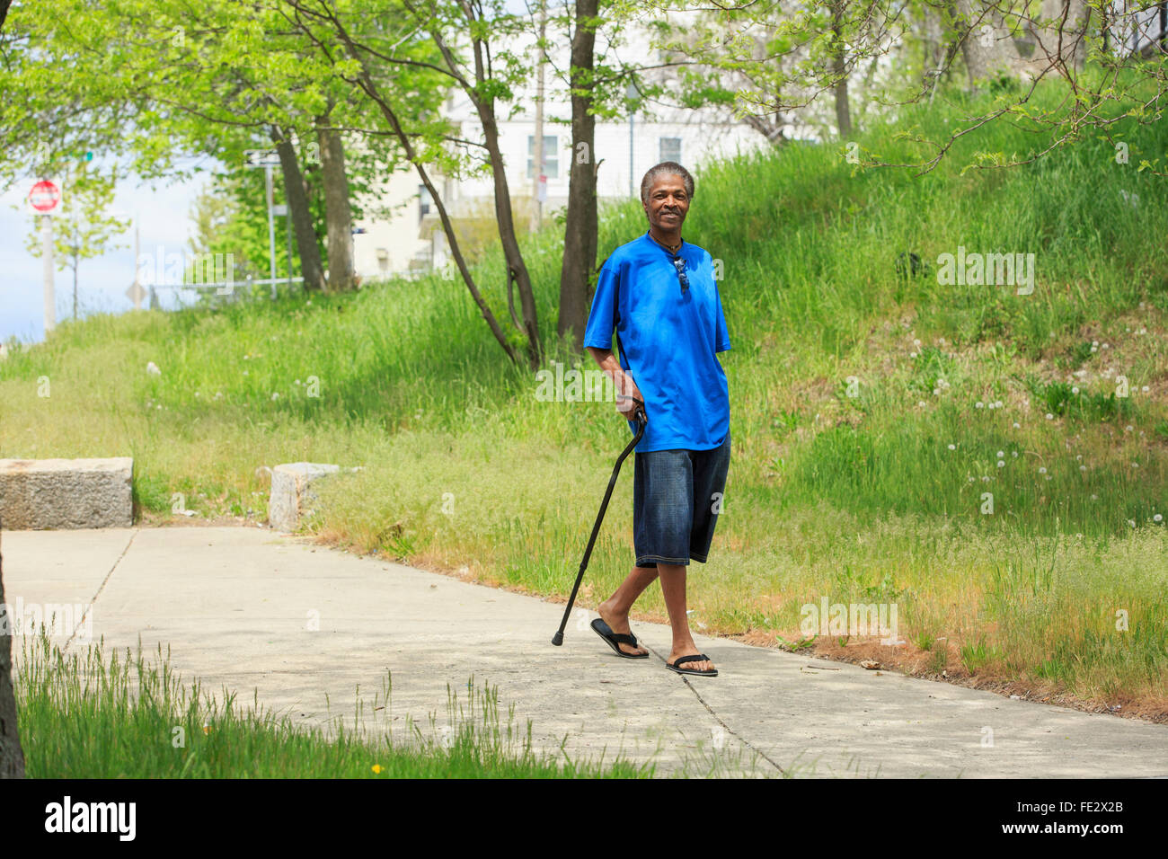 Man with Traumatic Brain Injury taking a walk with his cane - Stock Image