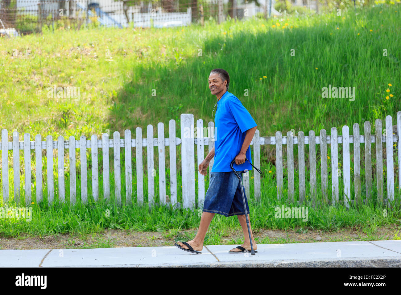 Man with Traumatic Brain Injury relaxing with his cane in his neighborhood - Stock Image