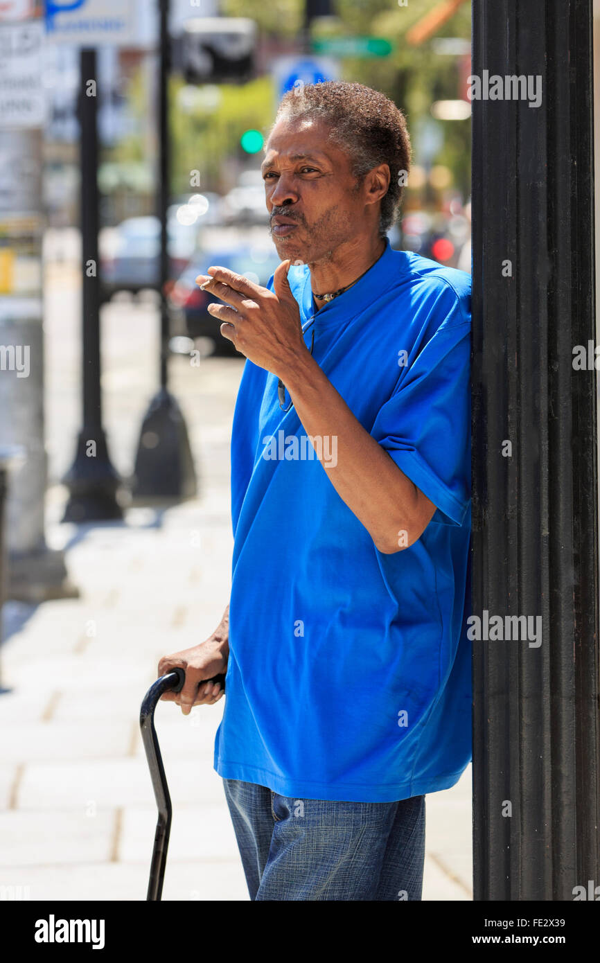 Man with Traumatic Brain Injury with cane smoking on the street - Stock Image