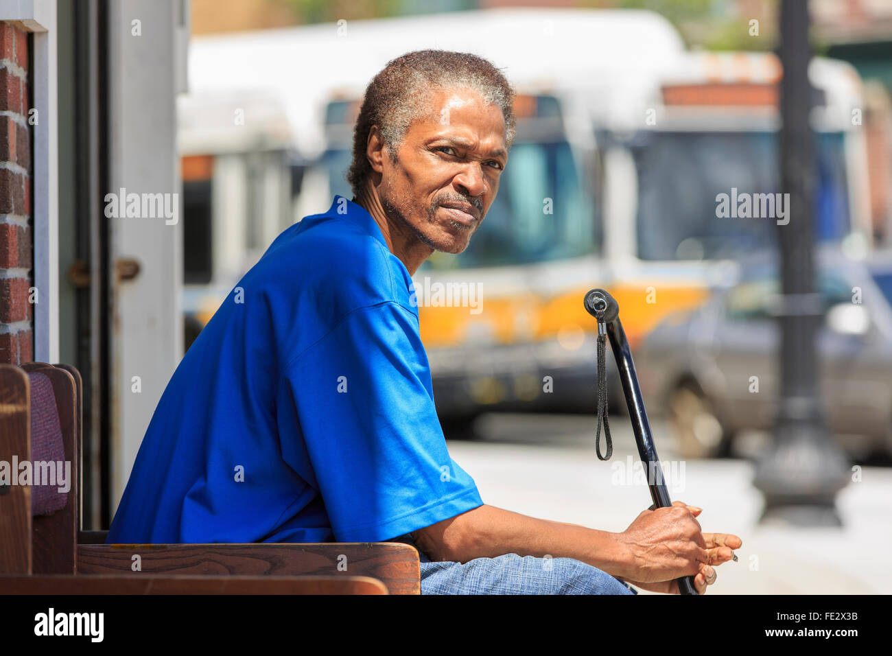 Man with Traumatic Brain Injury relaxing with his cane near the bus station - Stock Image
