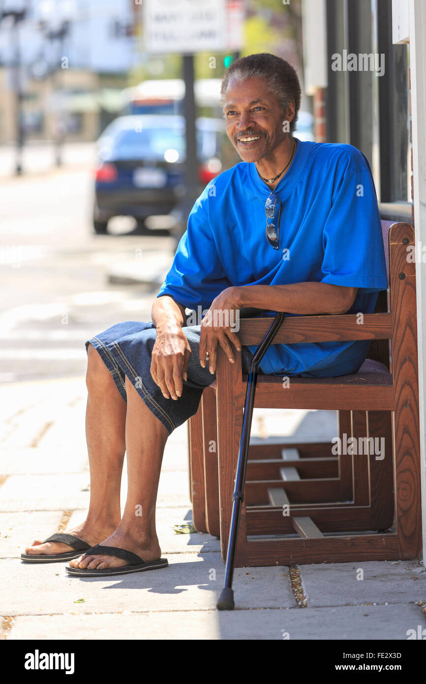 Man with Traumatic Brain Injury relaxing with his cane near the city street - Stock Image