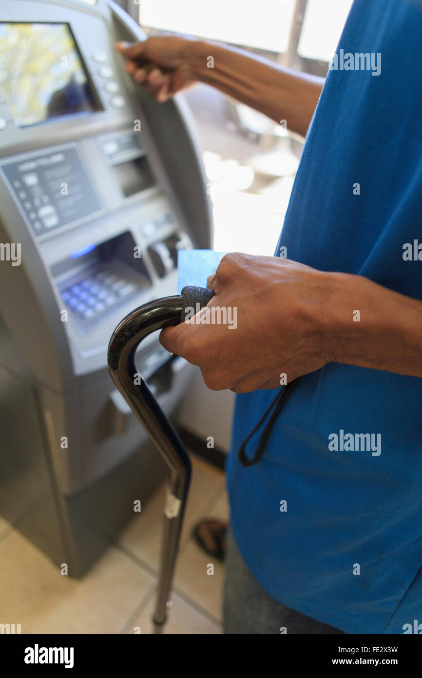 Man with Traumatic Brain Injury using a bank ATM - Stock Image