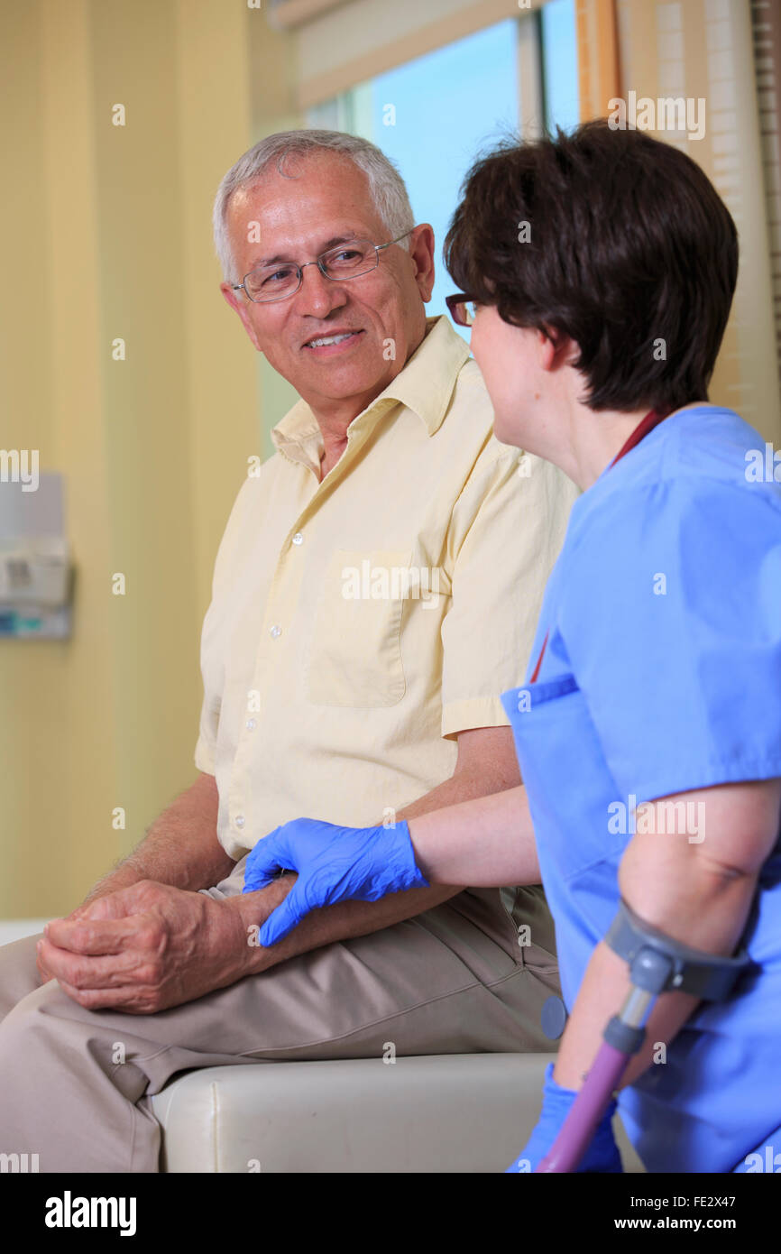 Nurse with Cerebral Palsy checking a patient's pulse rate in a clinic - Stock Image