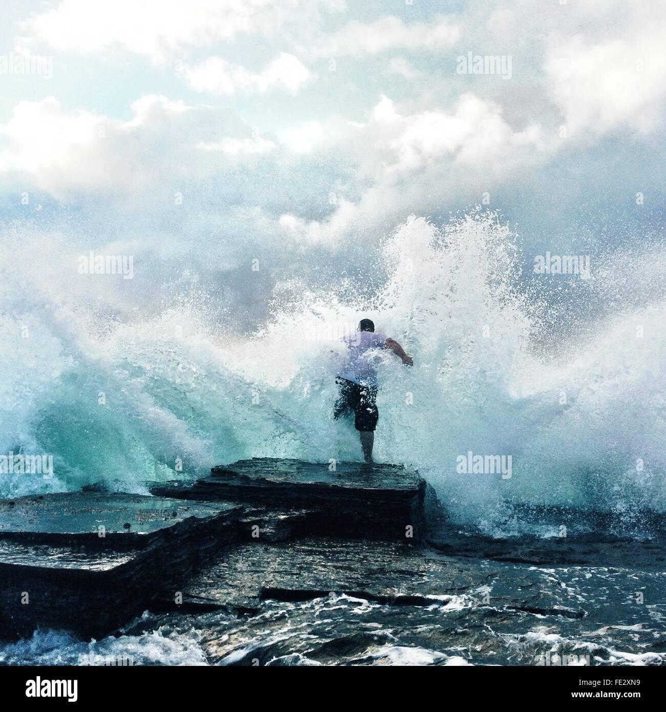 Waves Crashing At Rocks And Man - Stock Image