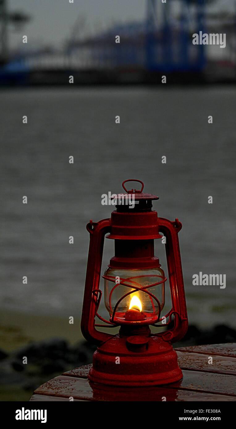 Close-Up Of Lit Antique Kerosene Lantern By Lake At Dusk - Stock Image