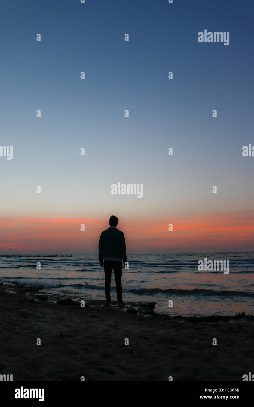 Full Length Rear View Of Man Standing At Beach During Sunset - Stock Image