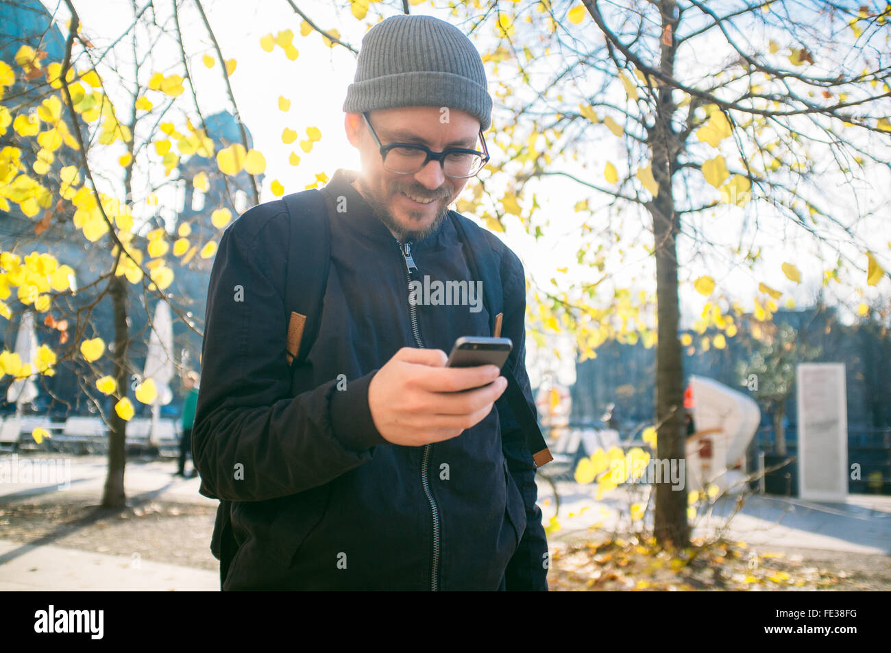 Smiling Mid Adult Man Using Phone On Footpath - Stock Image