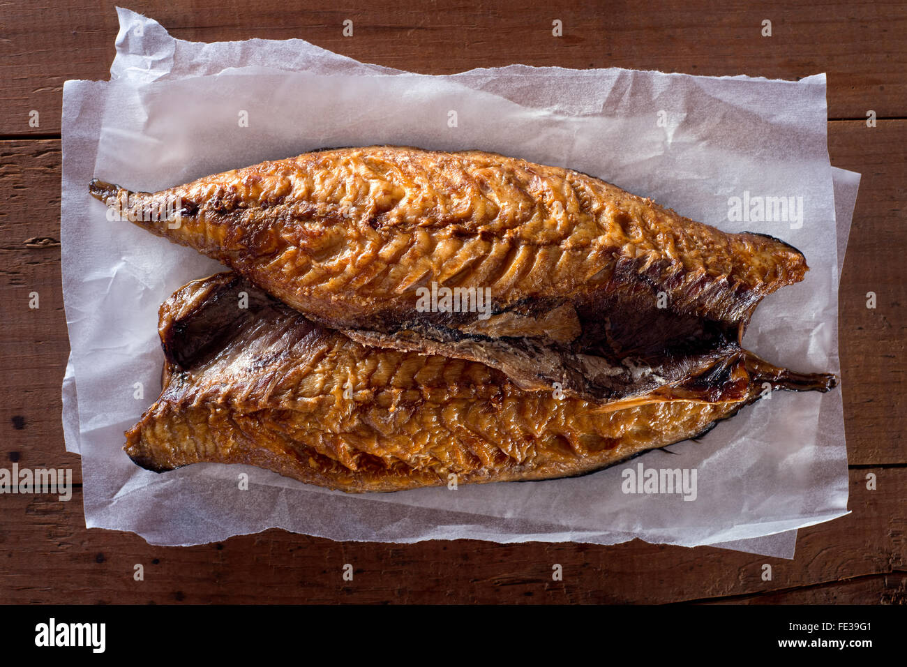 Smoked mackerel fillets on parchment paper against a rustic wooden background. - Stock Image