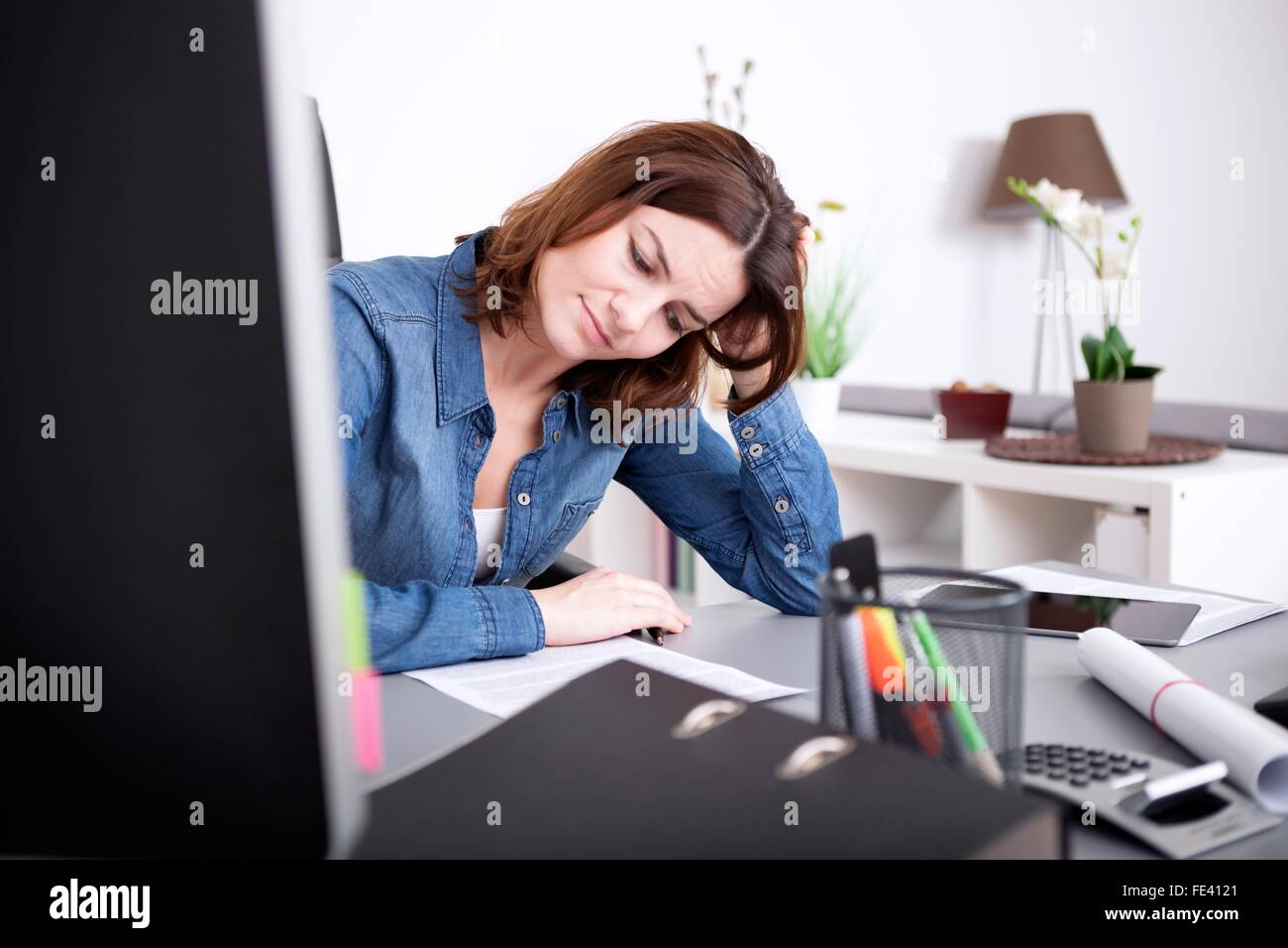 Attractive businesswoman working hard at the office sitting at her desk studying a paper document with a serious - Stock Image