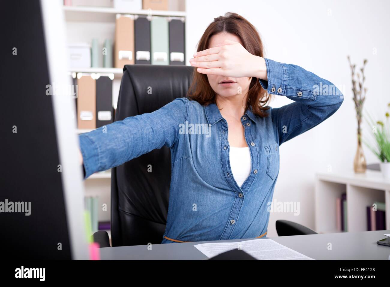 Businesswoman covering her eyes as she sits working at her desktop computer in the office as she tries to visualize - Stock Image