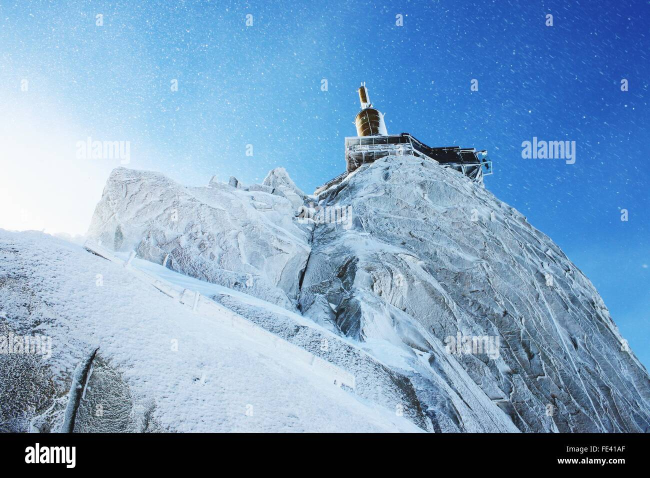 Low Angle View Of Aiguille Du Midi In Snow Against Blue Sky Stock Photo